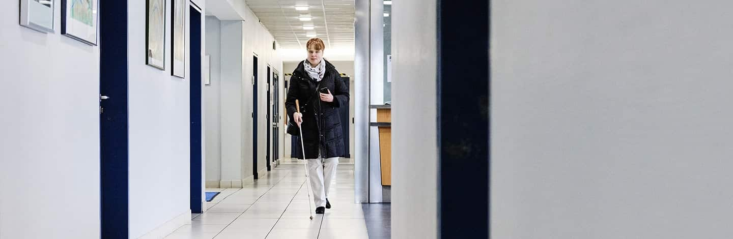 A woman (Sandra Pilz) who is blind using her white cane to guide her through the corridor of BFW Würzburg