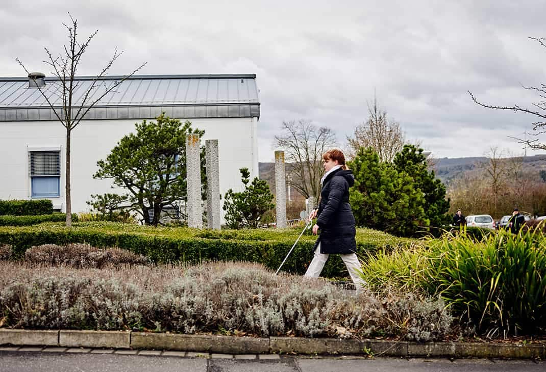 A woman (Sandra Pilz) who is blind using her white cane to walk on the green grounds of the BFW campus, with rolling hills in the background.