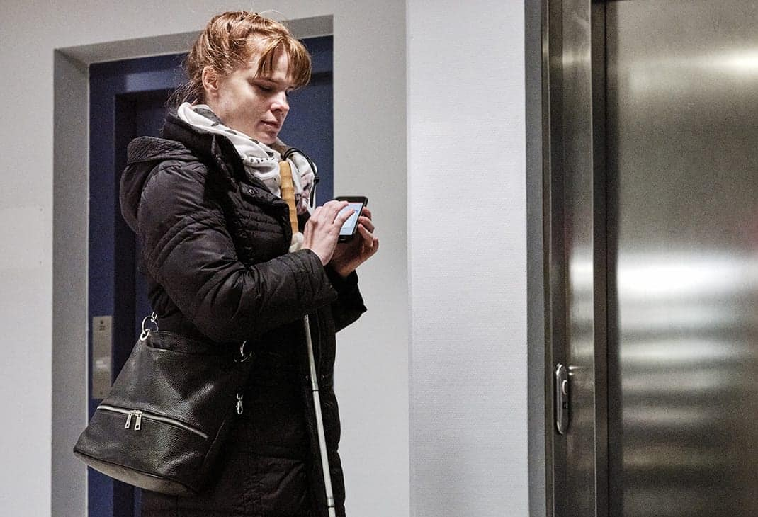 A woman who is blind using the BlindSquare application on her mobile phone in front of an elevator, white cane in hand.